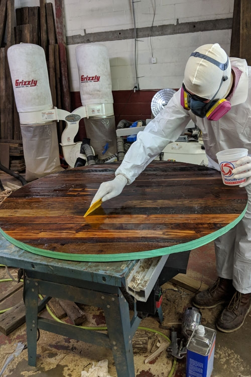 Michael Colemire applies a durable finish coat to the reclaimed barnwood dining tables.